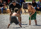 """The traditional stick game starts when one player holdng the """"tossel"""" drops it and the action begins. Adults provided on-field coaching of the young players and officiating the action."""