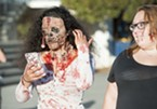 Selena Lopez checks her cell phone at the third annual Zombie Walk.