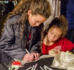 "Kehlan and Seryn Wester, of Arcata, write their ""wish"" ornament, which helpful elves placed in the tree-lighting ceremony."