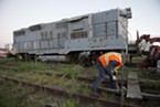 Brett Tallman, a friend of Matt Monson, who owns the locomotives, tightens a chain while crews from Humboldt Towing worked to get the engine on a front wheel assembly so that it could be moved to a more accessible piece of the Balloon Track property.