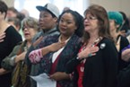 NAACP Eureka Branch President Liz Smith, second from right, and Donna Landry say the Pledge of Allegiance.