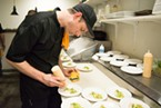 Graham Miller, Executive Chef of Mazzotti's puts the finishing touches of aioli on the sea scallop dish.
