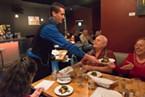 Kenny Evans delivers empanadas to patrons.