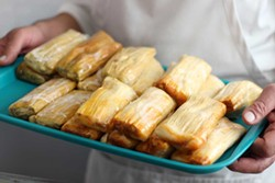PHOTO BY ANDREA JUAREZ - El Pueblo Market owner Engelberto Tejeda holds a tray of chicken and pork tamales. The two savory options, a vegetarian tamal and sweet corn tamal, are sold at his new Eureka market.