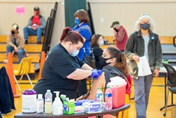 PHOTO BY MARK MCKENNA - Jennifer Price put a Band-Aid over the injection site of one of an expected 1,500 people to get a COVID-19 vaccine at Pacific Union School in Arcata on March 28.