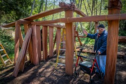 PHOTO BY MARK LARSON - Master Builder Walt Lara occasionally moved inside the framework of the women's Dressing House under construction to offer advice to a crew member.