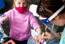 PHOTO BY KRIS NAGEL - A young participant gets a rainbow painted on their arm by local artist and face painter Abbie Perrott. The vaccination fair brought in families with children of all ages, though only those 12 and up could receive a dose of the vaccine.