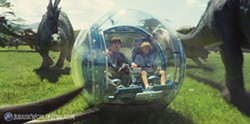 Children safely tucked in a hamster ball surrounded by dinosaurs. Seems legit.