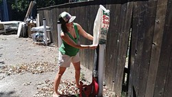 SUBMITTED PHOTO. - Holly Carter cleans bags with a leaf blower.
