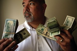 PHOTO BY FRANCINE ORR/LOS ANGELES TIMES - A Mendocino County district attorney investigator holds $45,000 in seized cash.