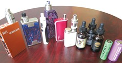 """PHOTO BY BARRY EVANS - Vapers have many choices beyond simple e-cigarettes, including these vaporizers shown here with """"e-juice"""" and batteries."""