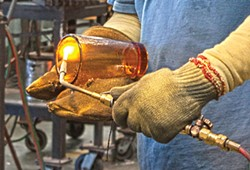 PHOTO BY CARRIE PEYTON DAHLBERG - A glass casting expert smoothes the finish on a Fire & Light pint glass in Arcata.