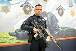 PHOTO BY MARK MCKENNA - Officer Ed Wilson holds two rifles EPD seized as evidence during a recent investigation.