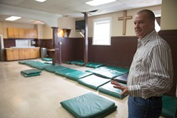 PHOTO BY MARK MCKENNA - Bryan Hall shows the mats that will be used for those in need of a safe night's sleep in the former dining hall at the Eureka Rescue Mission.