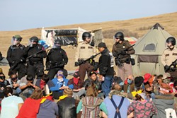 PHOTO BY ROB WILSON - A group of protesters locked arms to create a barricade against police during a Morton County sheriff-led push to remove demonstrators from the pathway of the Dakota Access Pipeline on Oct. 27.