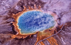 "PHOTO COURTESY JIM PEACO, NATIONAL PARK SERVICE - Huge mats of orange algae and bacteria surround Yellowstone's Grand Prismatic Spring in this aerial photo. ""Extremophiles"" like this could be the model for bioengineering life suited to extraterrestrial conditions."