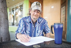 PHOTO BY MARK MCKENNA - Bob Hager writes in his notebook in front of Because Coffee in Eureka.