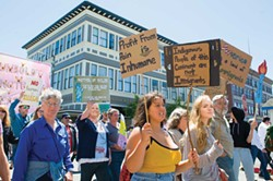 PHOTO BY MARK MCKENNA - Demonstrators march past the 10 Window Williams building in Old Town.
