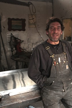 """PHOTO BY ZACH ST. GEORGE - Welder and private business owner Mike Powell in his Arcata shop. Powell said of the local economy, """"You draw a line and that's poverty, it seems like we're living on that line. It's like we're recession-proof in a way.""""'"""