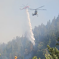 Our Fire, Our Fight When firefighters started a burnout near Jim Bennett's, it started a firestorm that carried fire across the Salmon River, where there had been no fire. Water drops from three helicopters plus a hotshot crew were needed to control it. Photo by Monkey Monk