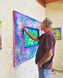 THE ARTIST AT WORK Los Osos artist Tom Sage puts the finishing touches on one of his colorful abstract works. - PHOTO COURTESY OF TOM SAGE ART