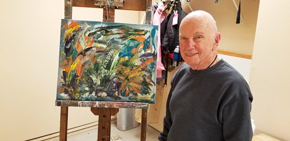 """GOING STRONG AT 93 Morro Bay author and artist Marvin Sosna, whose work is at the Cambria Center for the Arts this month, stands before """"Rising Tides,"""" which he says """"refers to Black Lives Matter, LGBTQ, the calls for justice and equality—a tsunami of long-restrained demand for action."""" - PHOTO COURTESY OF MARVIN SOSNA"""