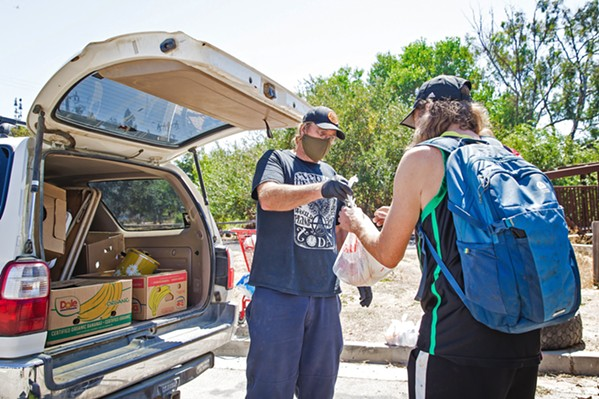 A HELPING HAND Paul Andreano, a volunteer with Hope's Village of SLO, hands out food to people living near the Bob Jones Trail, a popular homeless camp. - FILE PHOTO BY JAYSON MELLOM