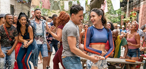 LA DANZA DE LA VIDA Usnavi (Anthony Ramos, left foreground) and Vanessa (Melissa Barrera, right foreground) take to the streets and dance with their neighbors, in the wildly entertaining and emotionally resonant musical, In the Heights, screening at most local theaters. - PHOTO COURTESY OF WARNER BROS.