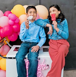 POPSICLE FUN (Left to right) Nolan Spears and Sophia Guzman enjoy a cold treat on top of the Paleta & Co. ice cream cart. - PHOTO COURTESY OF STEFANIE ELIZABETH PHOTOGRAPHY