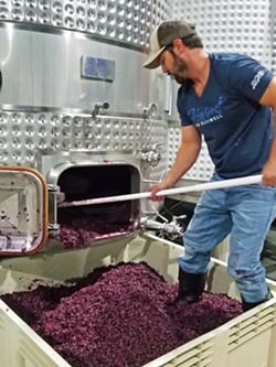 DIG IT Winemaker Jeff Huskey shovels skins following fermentation. Stay tuned for the future release of his 2019 vintage of 100 percent petit verdot. - PHOTO COURTESY OF RAGTAG WINE CO.