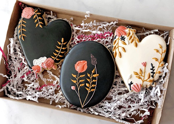 SWEETHEART Alexa Smith freehand designs many of her treats. A fellow baker provided the inspiration for her heart-shaped sugar cookies, then she fine-tuned the coloring and floral placement. - PHOTO COURTESY OF NIGHT SHIFT COOKIE CO.