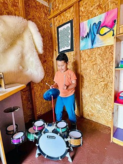 MAKING MUSIC A young Exploration Discovery Center patron makes some tunes in the Music Shed. - PHOTO COURTESY OF  EXPLORATION DISCOVERY CENTER