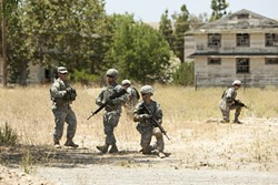 SIMULATED SITUATION :  A group of recruits practices methods for securing an improvised explosive device. By repeatedly drilling life-like scenarios, soldiers learn to react quickly and decisively to the real thing. - PHOTO BY STEVE E. MILLER