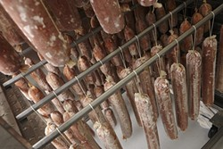 25: :  Inside the drying room, the freshly made salamis are on the racks in the bottom, while the ready to sell versions are hanging above.
