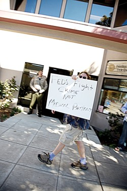 """ONE-MAN PROTEST :  As law enforcement agents wrapped up a raid in March 2007, Kent Connela paced the sidewalk with his homemade sign. """"You guys are no better than a gang,"""" he said. """"Waste of taxpayers' money, man."""" - FILE PHOTO"""