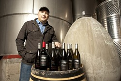 PROUD PATRIOT:  Nathan Carlson of Center of Effort wines stands with 11 examples of Patriots wine, - specifically sold at the New England Patriots Football team stadium. - PHOTO BY STEVE E. MILLER