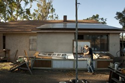 'A WORK IN PROGRESS' :  Jim Eickholdt at the Paso Robles home he shares with his wife and daughter. The family must now deal with alleged building code violations after NTF officers called the county building department following a search of the home. - PHOTO BY STEVE E. MILLER