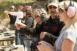 LINE UP :  Instructors John Marrs and John Odom teach safe gun techniques to (l-r) Suzanne Russell, Maeva Considine, Kelly Fontes, and Stephanie Ross. - PHOTO BY STEVE E MILLER