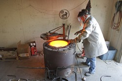 John Kemple prepares the furnace to begin pouring bronze. - PHOTO BY STEVE E. MILLER