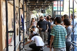 GUERRILLA ART! :  Co-organizer Neal Breton of San Luis Art Supply (he's the guy with the screw gun) helps donating artists mount their work on the wall of a construction barrier on Higuera Street, the scene of the last impromptu art show in which passersby were invited to take the work home for free. - PHOTO BY STEVE E. MILLER