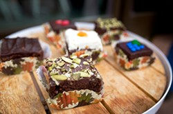 SQUARE DEAL:  A cluster of Heaven Squared brownies—including Pumpkin Spice Souffle (foreground), Blueberry Syrah, Ghost Chili, Apricot Cardamom Honey, and NBC (Nothing but Chocolate) tempt the taste buds as much as they intrigue the palate. - PHOTO BY KAORI FUNAHASHI