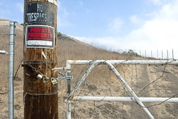 THIS LAND IS MY LAND:  Landowner Rob McCarthy has fenced off this entrance to the Ontario Ridge trail off Cave Landing Road near Avila Beach, aggravating many hikers and sparking a multi-party land-use skirmish. - PHOTO BY STEVE E. MILLER