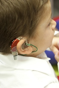 AMPLIFYING AID:  Preschooler Thomas's colorful hearing aid turns on a world of sound. - PHOTO BY STEVE E. MILLER