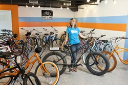 ELECTRIFYING RIDES:  One can buy or rent various models of Pedego electric bicycles in Avila Beach. Sandra Napua, director of marketing, stands behind the Trail Tracker model that can even be ridden on sand. - PHOTO BY STEVE E. MILLER