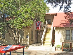 CONFEDERACY ON DISPLAY :  A confederate flag can be seen adorning the Crops House, with the same symbol painted across a table out front. - NEW TIMES STAFF PHOTO