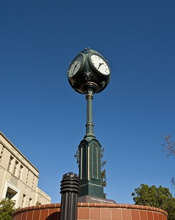 """BULBOUS:  In an intriguing takedown of the Volny Heritage Clock, which stands on the corner of Osos and Monterey Streets, political science major Lily Meryash humorously describes its """"bulbous clock head"""" which """"shoots up petrified as if caught somewhere it knows it's not supposed to be."""" - PHOTO BY STEVE E. MILLER"""