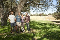 GRAPE MUSIC:  Over the shoulders of the Udsen family (Left to Right: Max, Niels, Bimmer, Luke, and Ruby the dog) lies the location of the stage for the Beaverstock music festival at Castoro Cellars. - PHOTO BY STEVE E. MILLER