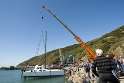 IN SHE GOES :  Nick Del Giorgio's 42-foot, 14-ton catamaran is lifted into the water for the first time. - PHOTOS BY STEVE E. MILLER