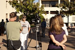 MAD AS HELL :  Becky Jorgeson, an advocate for the homeless, fielded questions from media and a Los Angeles-based documentary film crew in front of the San Luis Obispo County Superior Courthouse on Sept. 7 while protesting an alleged lack of services for the local homeless population. - PHOTO BY STEVE E. MILLER