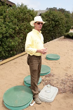 Tom Murphy, inventor of the Reclamator sewage recycling system, stands in front of the only installed system in Los Osos to date. - PHOTO BY STEVE E. MILLER